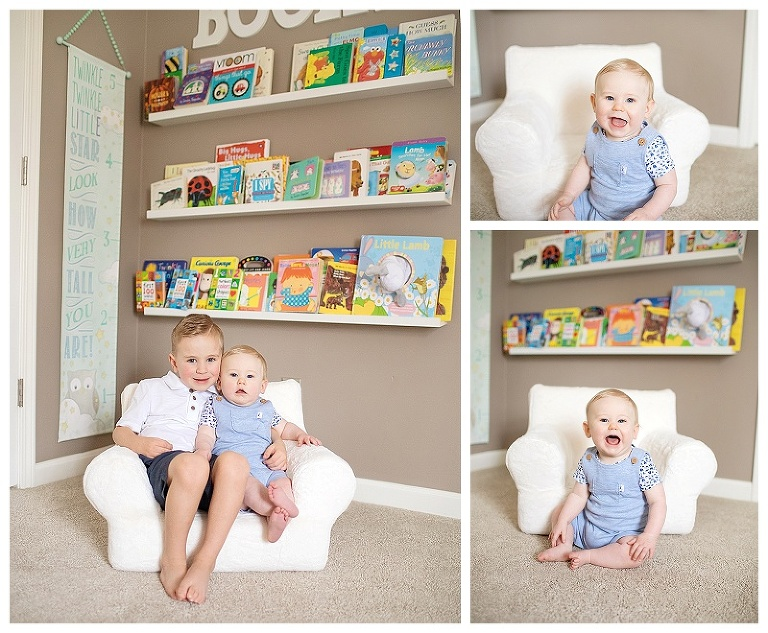 Little boy with his baby brother in the nursery in front of their shelves of books.  Baby is smiling for the photographer.